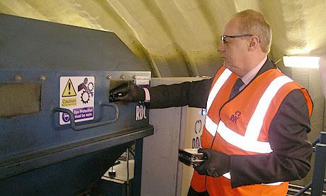 Minister Damian Green puts ID card hard drive into shredder